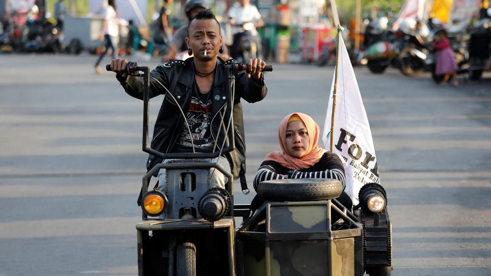 Extreme Vespa enthusiasts drive near the site of a scooter festival in Kediri, East Java, Indonesia. Every year, Indonesians from teens and grandads, to mechanics and students, gather in eastern Java to celebrate their love of the iconic Italian scooter. (Darren Whiteside / REUTERS)