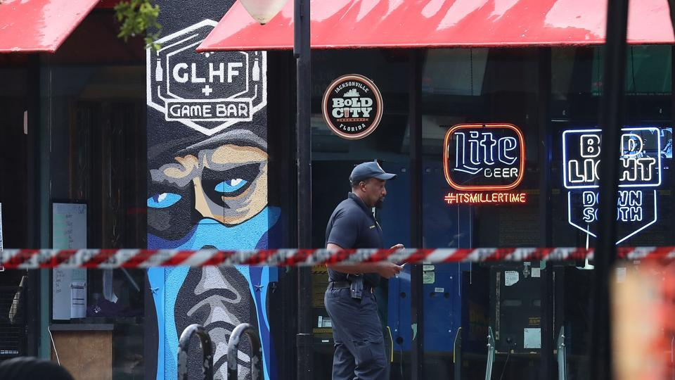 A Jacksonville Sheriff officer walks past the GLHF Game Bar where 3 people including the gunman were killed on August 27, 2018.