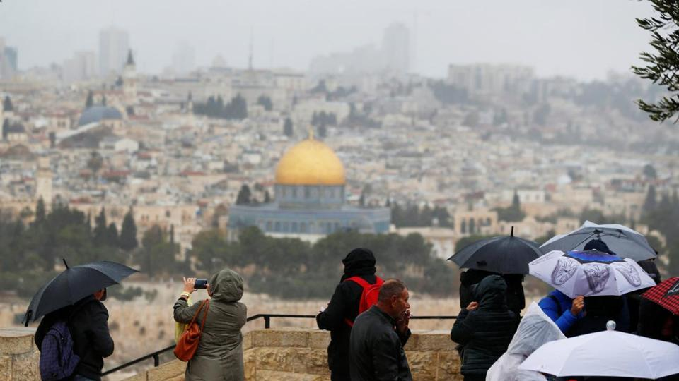 People stand at an observation point overlooking the Dome of the Rock and Jerusalem's Old City.