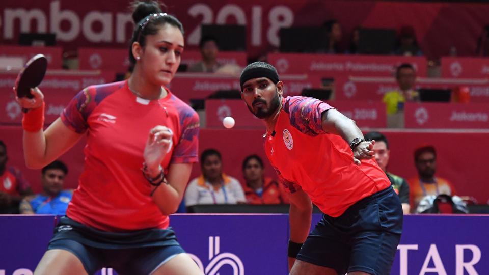 India's Sharath Kamal Achanta (R) watches as teammate Manika Batra returns the ball in the table tennis mixed doubles semi-final against China's Sun Yingsha and Wang Chuqin during the 2018 Asian Games.