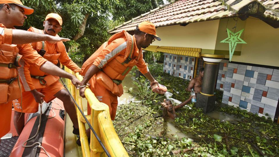 Members of the National Disaster Response Force distribute food, water and medicines to flood victims at Alappuzha district, Kerala, August 20, 2018
