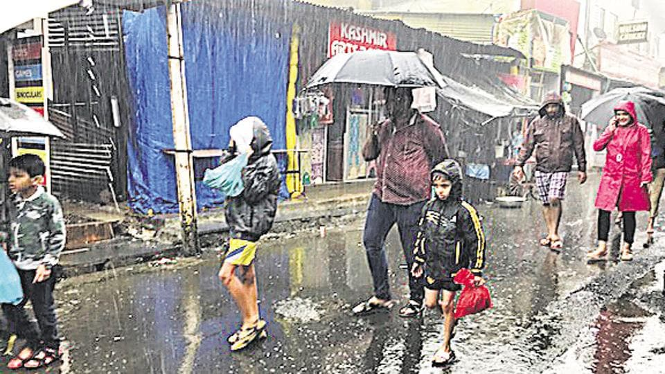 Tourists in Mahabaleshwar walk through a drenched and shut main market area, with the hill station soaking in rain.