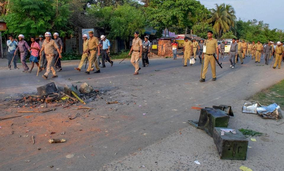 Security personnel walk past burnt ballot boxes lying on a road after violence  during panchayat elections in Rampur in South Dinajpur district of West Bengal in May.