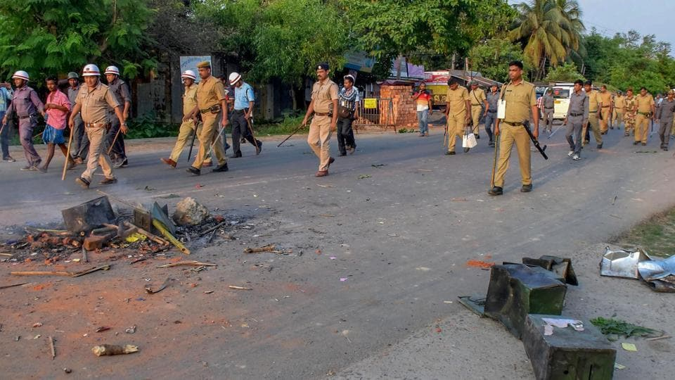 Security personnel walk past the burnt ballot boxes lying on a road after a polling station was ransacked during panchayat polls at Rampur in South Dinajpur district of West Bengal, May 14, 2018.