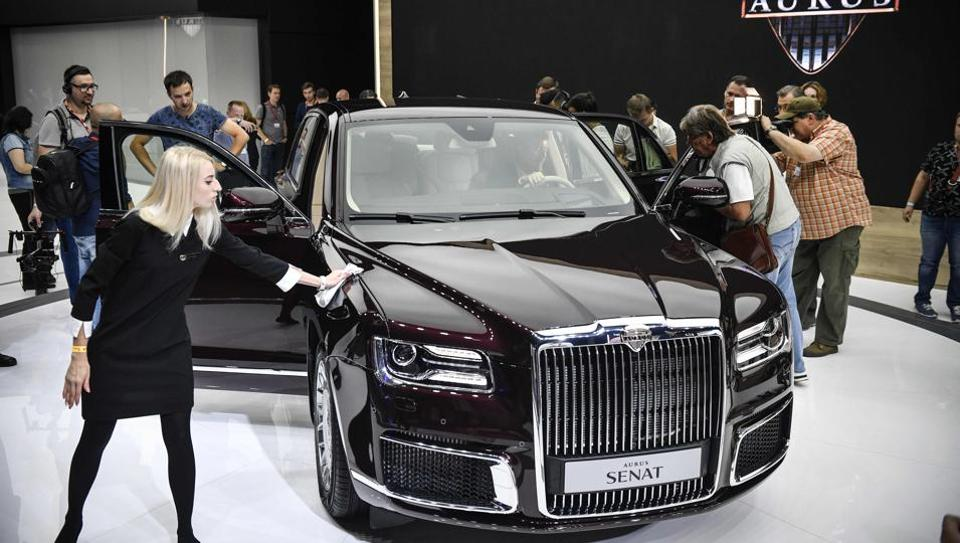 Visitors inspect a sedan version of Russian President Vladimir Putin's new Argus Senat limousine at the Moscow International Motor Show in Moscow on August 29, 2018.