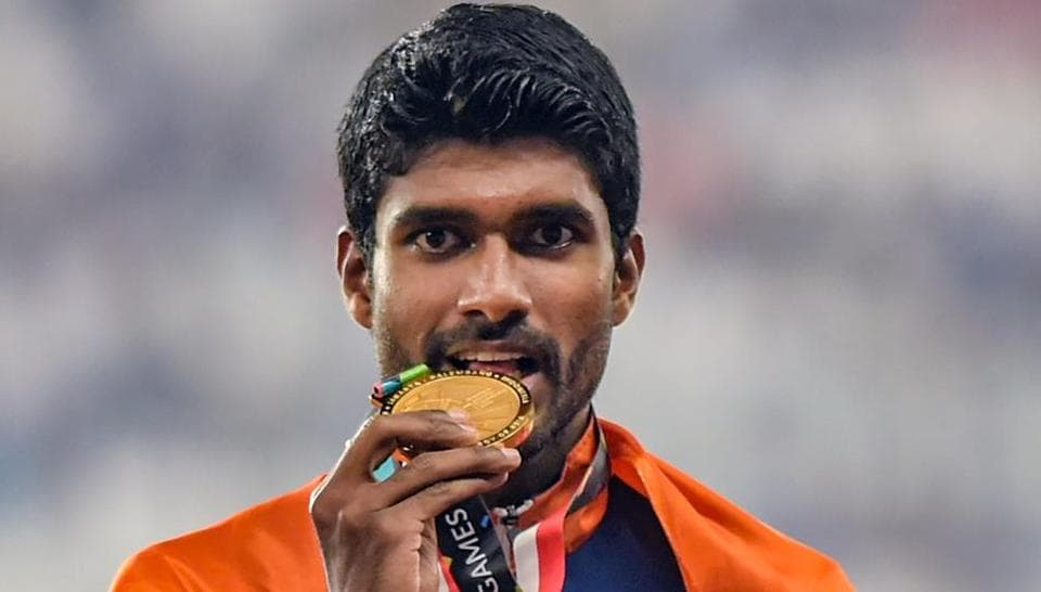 Gold medallist athlete Jinson Johnson poses for photographs during the medal ceremony for the men's 1500m event. (PTI)