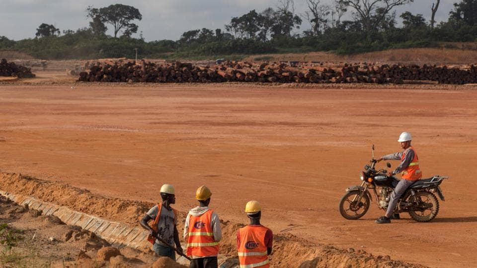 A CHEC employee sits on a motorcycle as he speaks with workers digging near to the Port of Kribi. Since the initial agreement to build the port at Kribi was signed in 2009, 10 Chinese firms, including CHEC and its holding company, China Communications Construction Co., have obtained concessions to mine bauxite, iron ore and other minerals in Cameroon. (Adrienne Surprenant / Bloomberg)