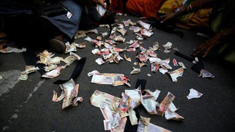Pieces of old fake 1000 rupee notes lay on the street during a protest, organised by  Congress party, to mark a year since demonetisation was implemented by Prime Minister Narendra Modi, in Ahmedabad, India.