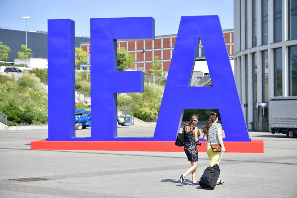 Women pass by an IFA logo at the entrance of the upcoming IFA, the world's leading trade show for consumer electronics and home appliances, in Berlin on August 29, 2018.