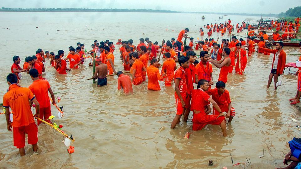 Kanwariyas take a dip in the river Ganga on the first day of holy month of Shravan, at Vindhyachal dham in Mirzapur.