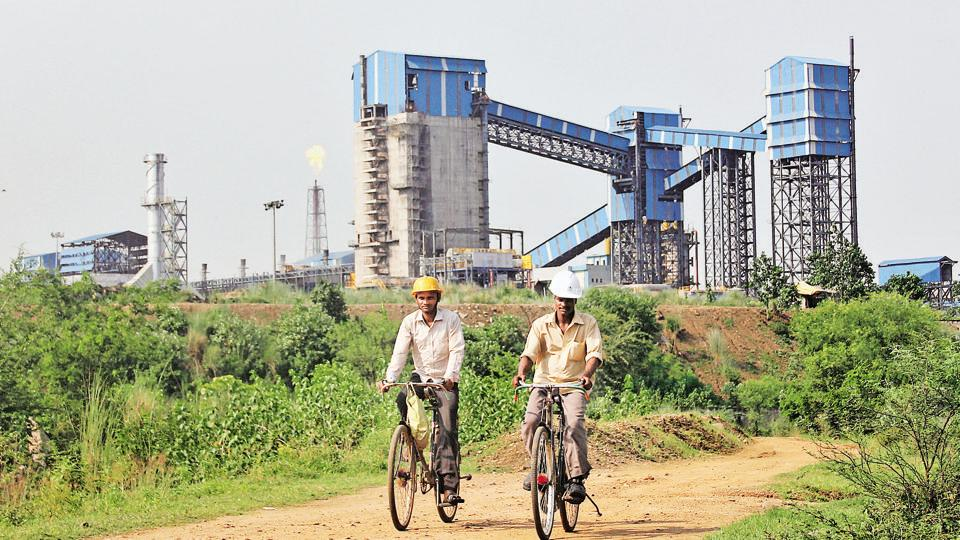 Men ride their bicycles in front of the Bhushan Steel plant in Odissa.