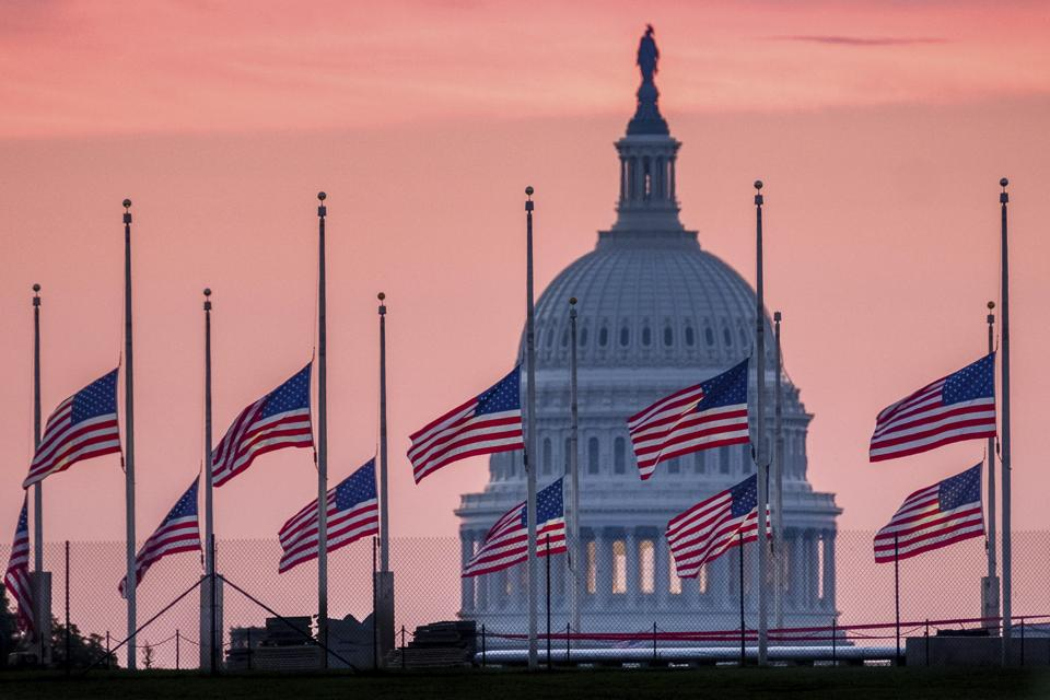 Flags, flying a half-staff in honour of Senator John McCain, frame the US Capitol at daybreak in Washington.