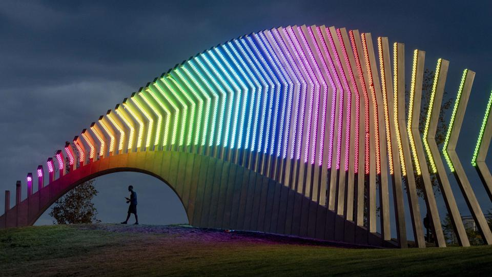A man walks under Moving Surfaces, a giant steel and light sculpture at Ottawa's Lansdowne Park, as it is lit up in the colours of the rainbow, during Pride Week. (Justin Tang / The Canadian Press via AP)