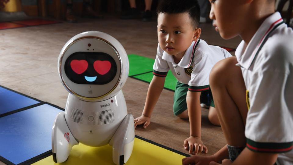 Children watch a Keeko robot make its way on a path they made from square mats at the Yiswind Institute of Multicultural Education in Beijing. (Greg Baker / AFP)