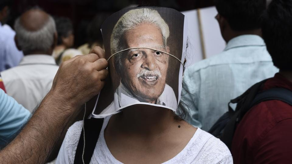 A protester adjusts a portrait of poet Varavara Rao on the face of another protester during a demonstration in New Delhi on August 30, 2018. The Supreme Court (SC) on Wednesday however, stopped Pune police from taking custody of five activists, and placed them under house arrest in their respective homes until the case is heard again on September 6. (Burhaan Kinu / HT Photo)