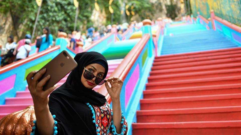 A woman takes selfies in front of the newly-painted 272-steps staircase leading to Malaysia's Batu Caves Hindu temple in Kuala Lumpur, Malaysia. (Manan Vatsyayana / AFP)