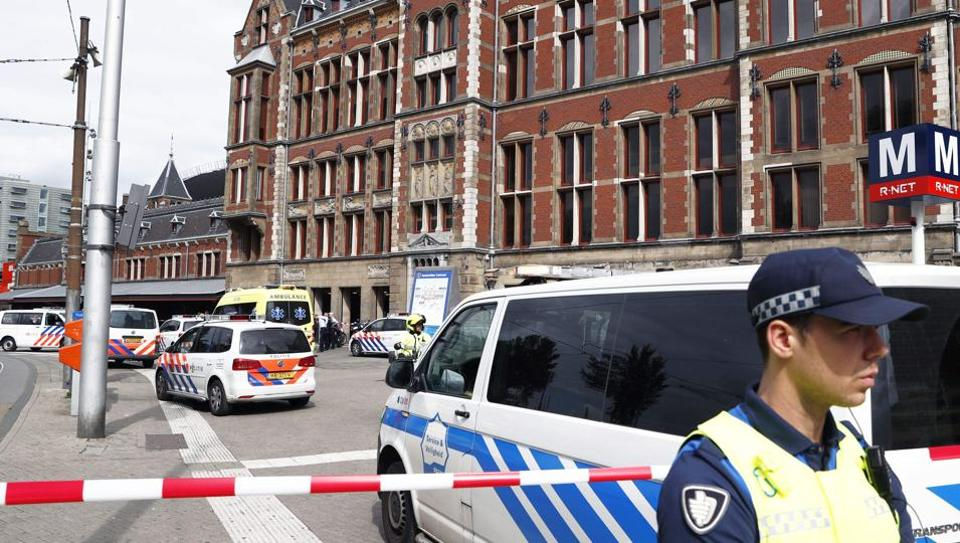 A security official stands beside a cordonned-off area at The Central Railway Station in Amsterdam on August 31, 2018, after two people were injured in a stabbing incidnet.