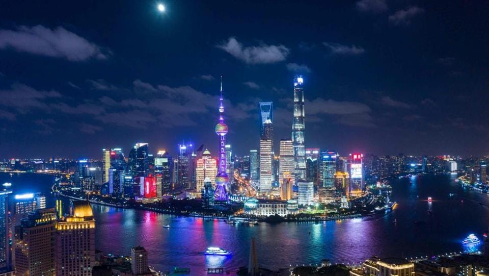 The moon shines over the financial district of Pudong in Shanghai. (Johannes Eisele / AFP)