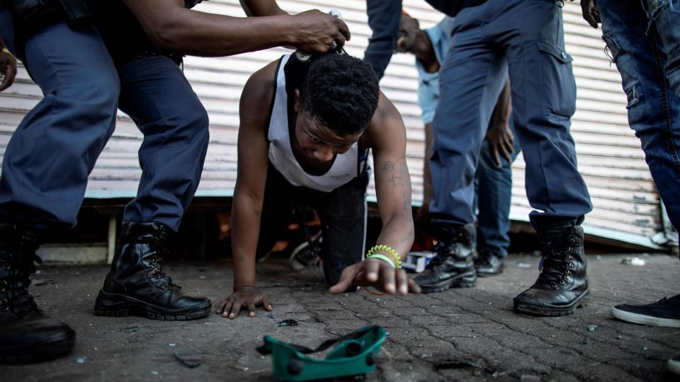 A suspected looter is detained by South African police officers as he emerges from a looted foreign-owned shop in Soweto, Johannesburg during unrest that erupted after a foreign shop owner allegedly shot and killed a member of the community during a demonstration. (Marco Longari / AFP)