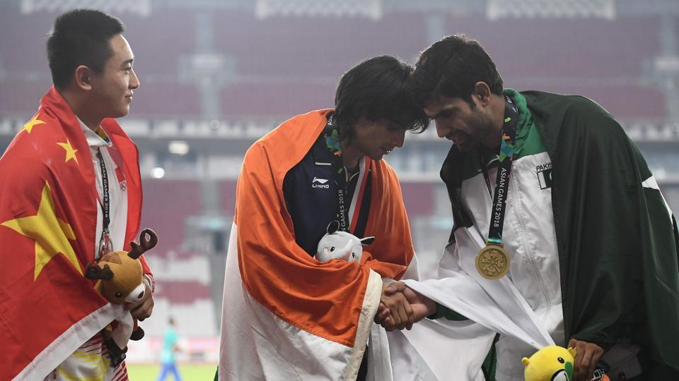 (L-R) Silver medallist China's Liu Qizhen watches as gold medallist India's Neeraj Chopra shakes hands with bronze medallist Pakistan's Arshad Nadeem during the victory ceremony for the men's javelin throw athletics event during the 2018 Asian Games in Jakarta, Indonesia. (Jewel Samad / AFP)