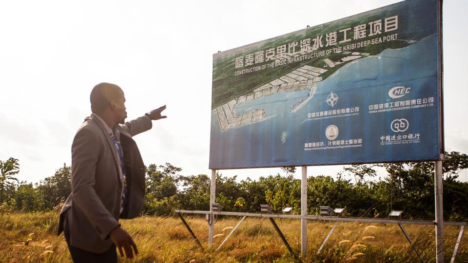 "James Arthur Edongue, chief port logistics for the Port Authority of Kribi, explains a mandarin language CHEC billboard. Delays have also plagued the project. Last year's bankruptcy of the French logistics company NCT Necotrans meant the government had to postpone the opening of the container terminal. Despite stiff French competition, CHEC managed to persuade Cameroon that it was able to ""realise its dream."" (Adrienne Surprenant / Bloomberg)"