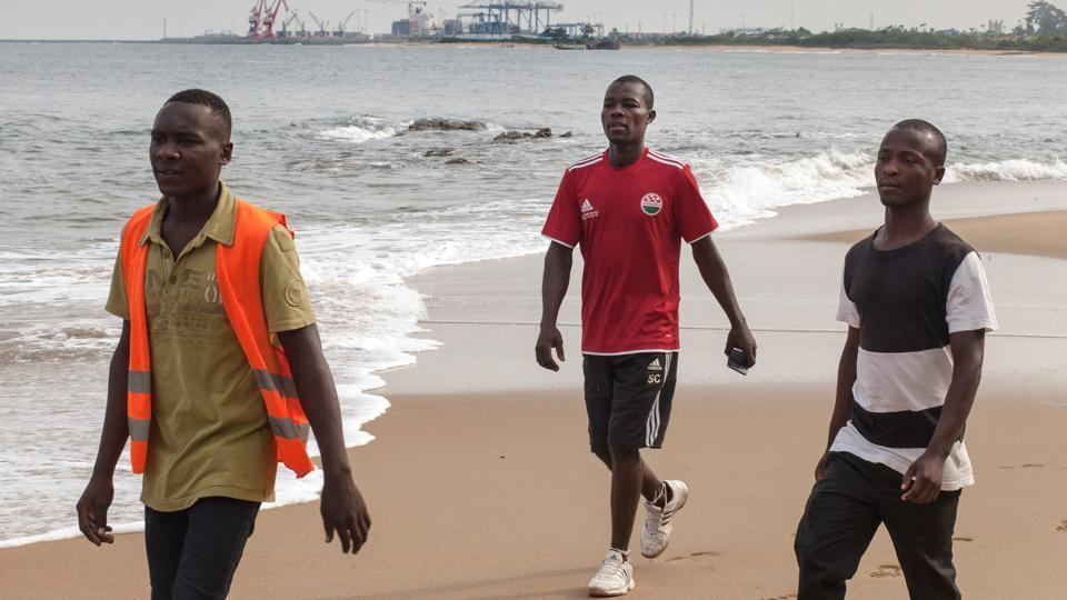 Alain Eko(C), 34, walks with colleagues along Lolabe beach. Every day at sunrise, Eko walks half an hour on a footpath cutting through a coastal forest to the edge of what's to become the biggest deep-water port in central Africa. He has offloaded trucks, wedged bricks into hill slopes and shoveled dirt since he moved here to work as a day labourer with contractors for the company building the port, China Harbour Engineering Co.(CHEC). (Adrienne Surprenant / Bloomberg)
