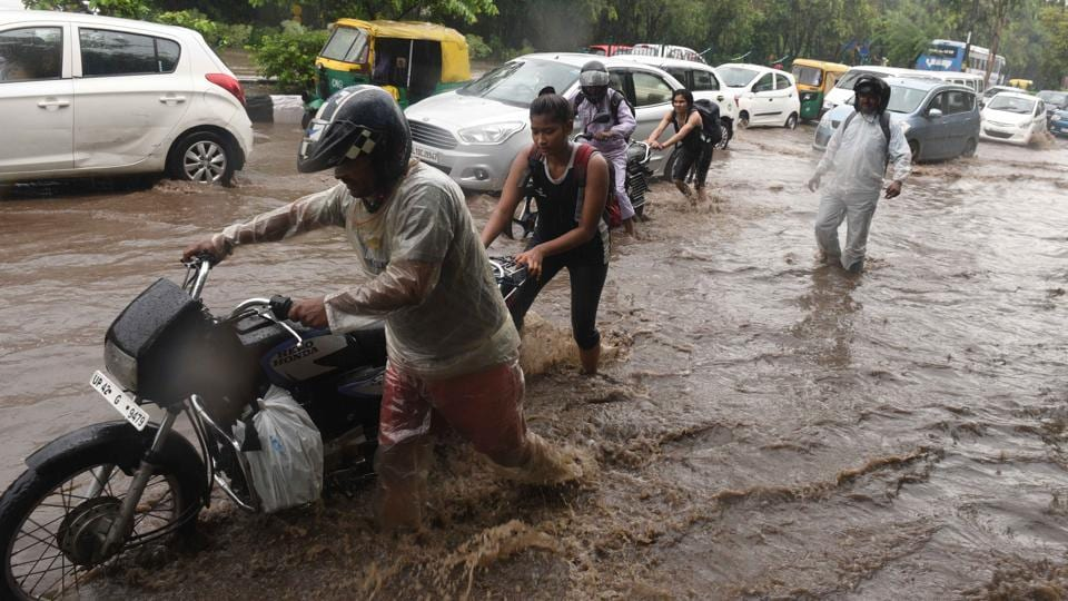Their day's practice at Indira Gandhi Stadium cancelled, good Samaritans helped commuters stuck on inundated roads at Ring Road ITO. The minimum temperature was recorded at 23.5 degrees Celsius, three notches below the season's average, while the maximum temperature was likely to be around 32 degrees Celsius. (Sonu Mehta / HT Photo)