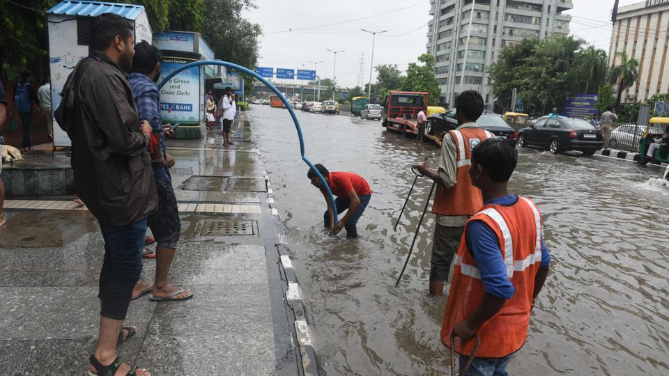 Civic workers work to unclog drians by the roadside near at Inderprastha Marg near the Delhi Police headquarters. An IMD bulletin on Saturday morning said that though the cross equatorial flow associated with the southwest monsoon has weakened, the monsoon trough, especially its eastern part, is likely to remain active during next few days, making major rainfall likely to north and adjoining central India. (Sonu Mehta / HT Photo)