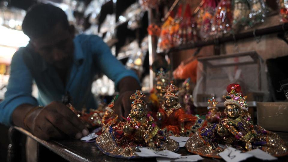A shopkeeper displaying idols of Hindu Lord Krishna ahead of 'Janmashtami' or birth of Lord Krishna in Jammu.  (Nitin Kanotra /ht)