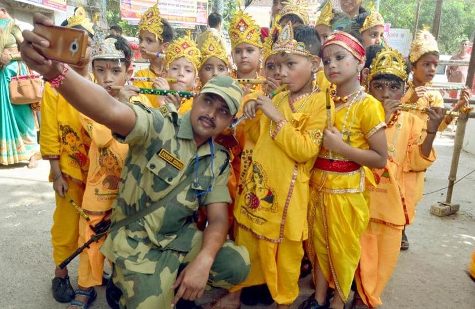 An Indian Border Security Force (BSF) jawan clicking a selfie with school children, dressed as Lord Krishna during Krishna Janmashtami celebrations at Durgiana Temple in Amritsar on Saturday.  (Sameer Sehgal/ht)