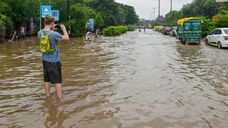 A person takes a photo while standing on a waterlogged street following monsoon rains, in New Delhi on Sunday, Sept 2, 2018.