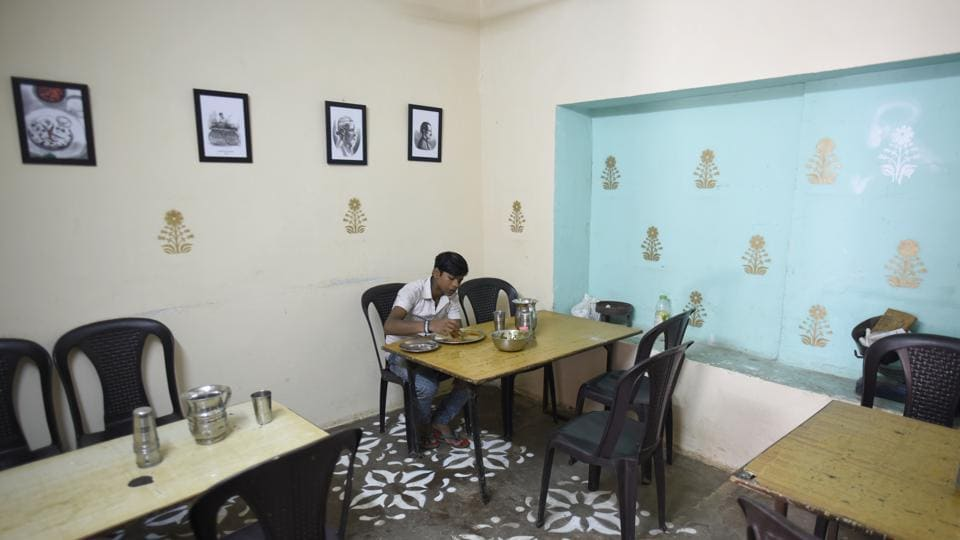 The logo for 'vaishno dhaba' features Chalittar Mukhiya, the owner, who started the dhaba in the 1990s. The inside walls have stencil art with photos of his father and him as a young man selling food on a cart; a chalkboard as a menu. Choudhury said he wanted a nostalgia-driven design, inspired by vintage coffee house aesthetics, which remained functional for Mukhiya and his clients. (Burhaan Kinu / HT Photo)