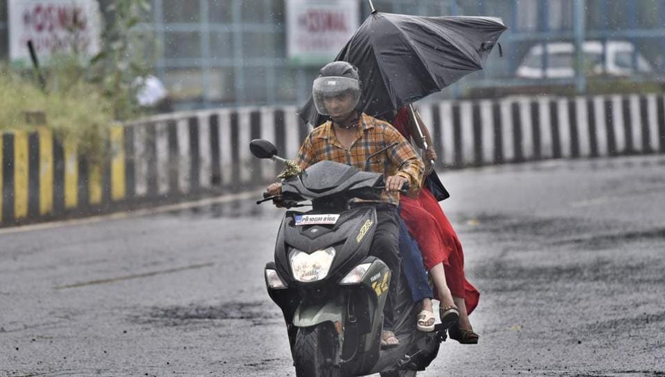 Commuters holding the umbrella to protect themselves from the rain at Ferozepur road in Ludhiana on Monday.