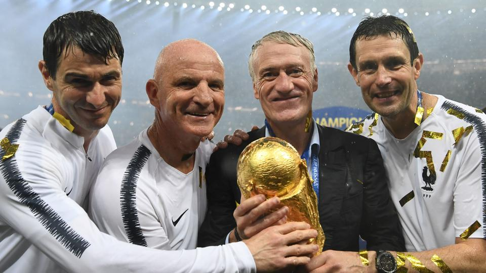 France's coach Didier Deschamps poses with the World Cup trophy.