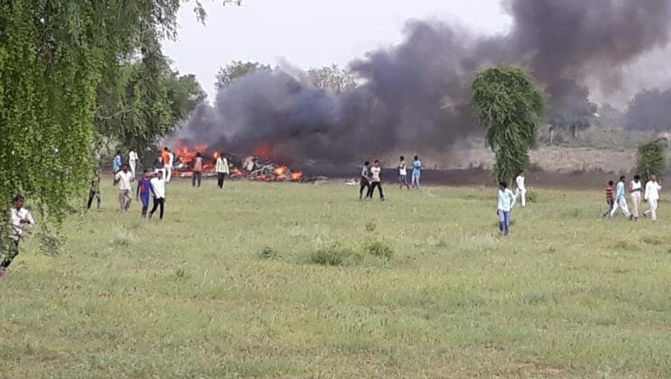 Locals rush to the crash after a MiG 27 jet went down in Jodhpur on Tuesday morning.