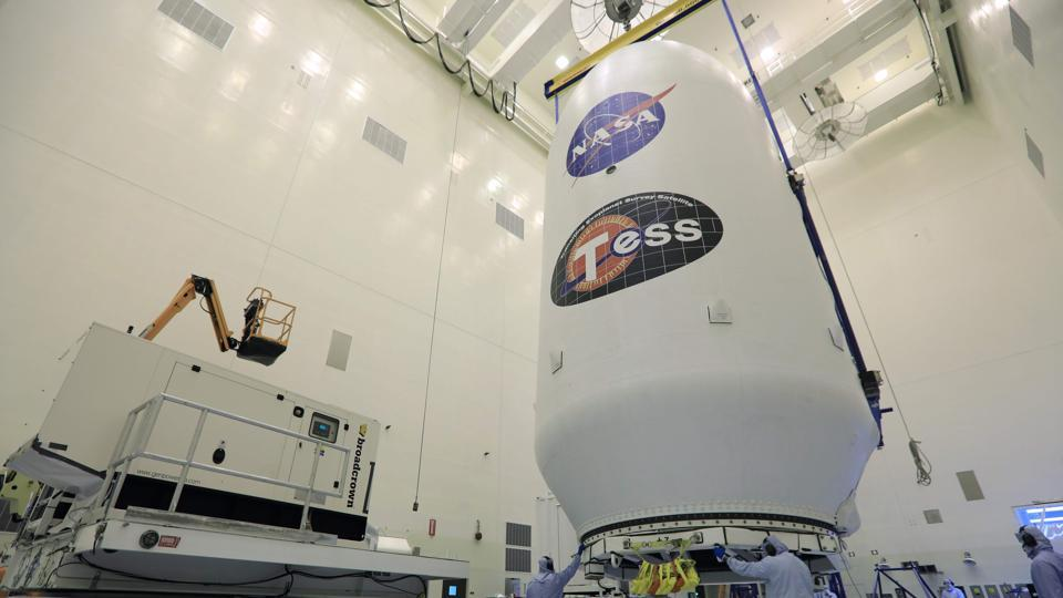In this file photo taken on April 11, 2018 obtained from NASA, technicians assist as the SpaceX payload fairing containing the NASA's Transiting Exoplanet Survey Satellite (TESS) is moved to a transporter, at NASA's Kennedy Space Center, Florida.