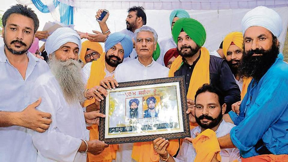 Punjab Congress chief Sunil Jakhar, flanked by ministers Balbir Singh Sidhu and Navjot Singh Sidhu, receives a memento carrying the photographs of the two victims of the Behbal Kalan police firing, at a rally in the village on Wednesday.