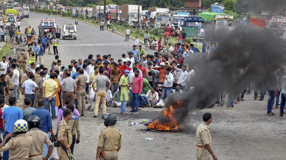 Several upper caste organisation activists raise slogans and burn tyres during Bharat Bandh protest called over SC/ST Amendment Act, in Varanasi, Thursday.