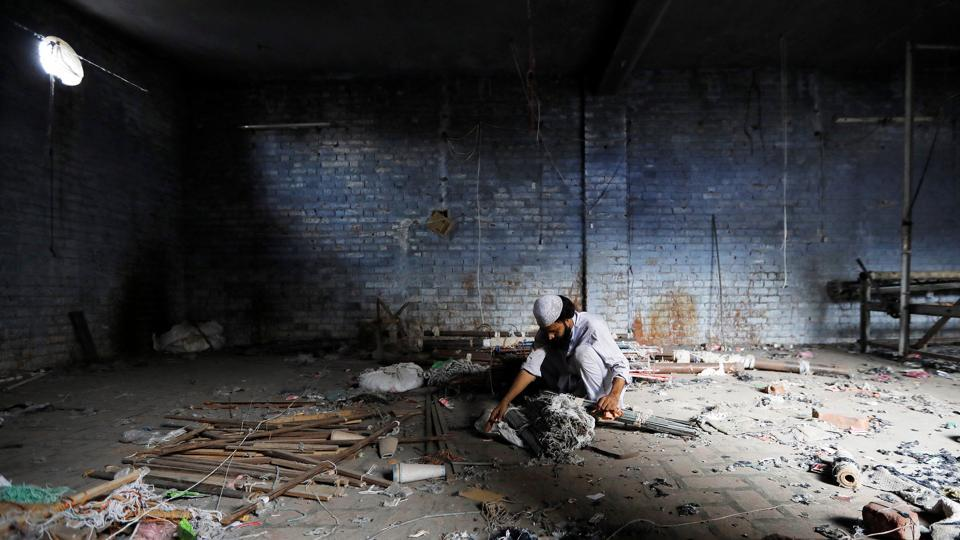 A scrap dealer searches for useful material at a weaving factory that was shut a year ago, in Panipat, Haryana. India launched the Goods and Services Tax (GST) just over a year ago, its biggest ever tax reform, aiming to replace more than a dozen federal and state levies and unify the sprawling economy. (Adnan Abidi / REUTERS)