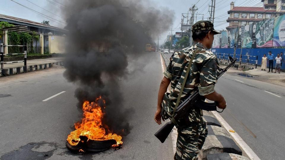 A security personnel walks past a burning tyre during a protest against fuel price hike and depreciation of the rupee in Guwahati. Tens of people were detained in Assam from multiple districts after they tried to block roads and highways to enforce the shutdown, a senior police official said. However, the Bandh has paralysed normal life as buses and taxis kept off the roads. (PTI)