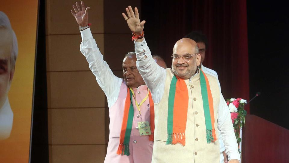 BJP national president Amit Shah with party's Rajasthan president Madan Lal Saini waves to party members during a meeting at Birla Auditorium, in Jaipur on September 11.
