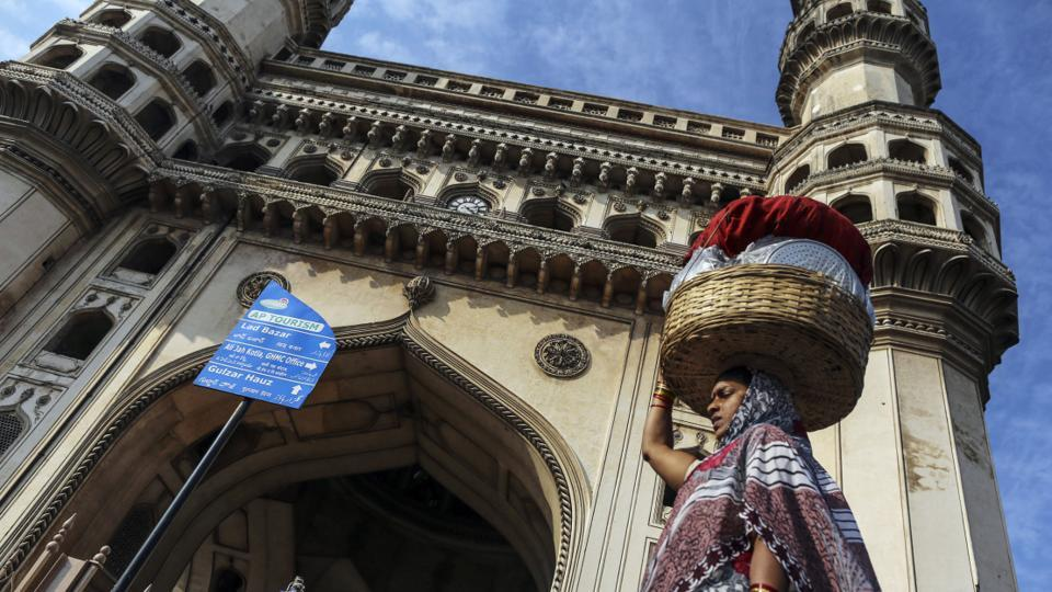 A woman carries a basket of goods on her head while walking past Charminar monument and mosque in Hyderabad.