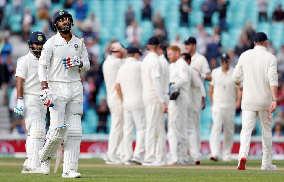 India's K. L. Rahul (2L) walks back to the pavilion after losing his wicket for 149.