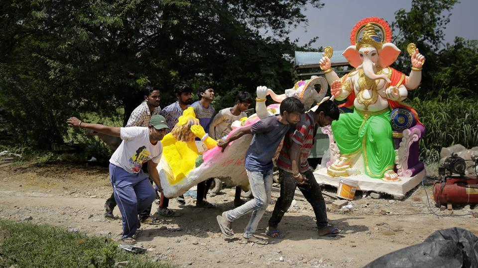 People carry an idol of Ganesha at a workshop in New Delhi, ahead of the 'Ganesh Chaturthi' festival that celebrates the birth of the elephant headed god. (Altaf Qadri / AP)