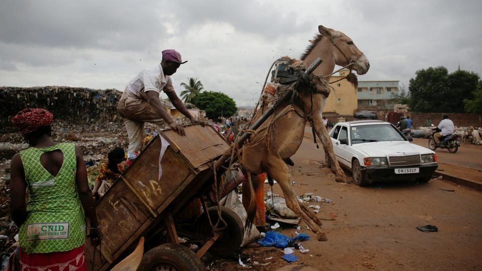 A waste picker unloads garbage at a waste transfer station in Bamako, Mali. In the Malian capital of Bamako, donkey carts driven by young men like 19-year-old Arouna Diabate play a vital role battling the fast-growing city's waste problem. (Luc Gnago / REUTERS)