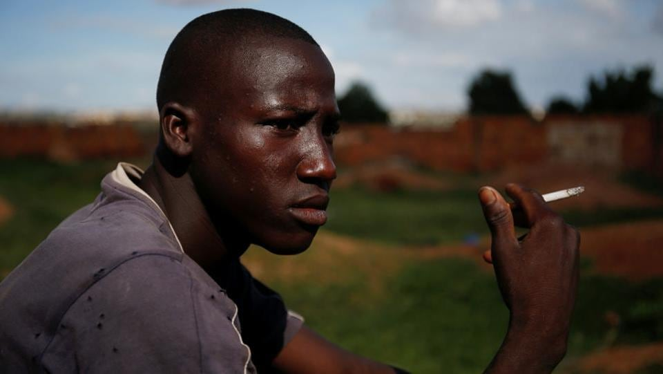 "Arouna Diabate, 19, smokes as he sits at the donkey pasture. Diabate receives a monthly salary of around $35 at his trash collection job. ""I won't be picking up trash with a donkey cart for the rest of my life, but for now people appreciate us because we help clean up the homes of Bamako,"" he said. (Luc Gnago / REUTERS)"