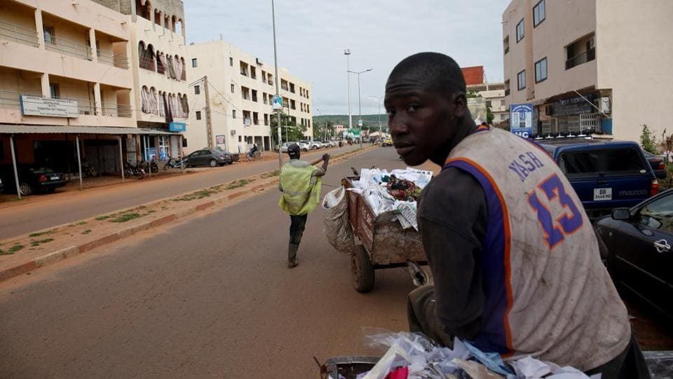 Arouna Diabate, 19, drives his cart as he works in Bamako. Every morning before dawn, Diabate hitches his donkey to a cart and sets off on his rounds, going door-to-door to collect household garbage. (Luc Gnago / REUTERS)