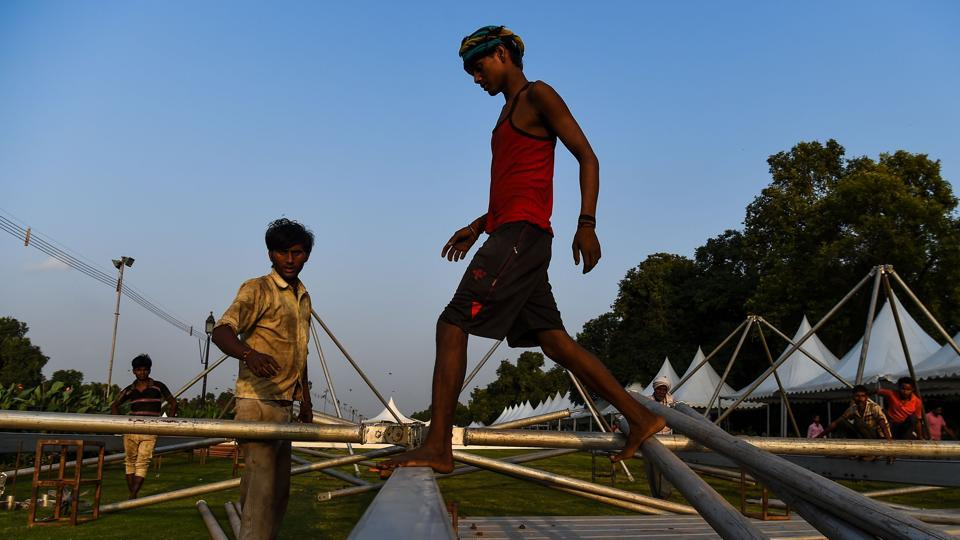 Labourers work at the lawns of Rajpath near India Gate in New Delhi on September 12, 2018. (Chandan Khanna / AFP)