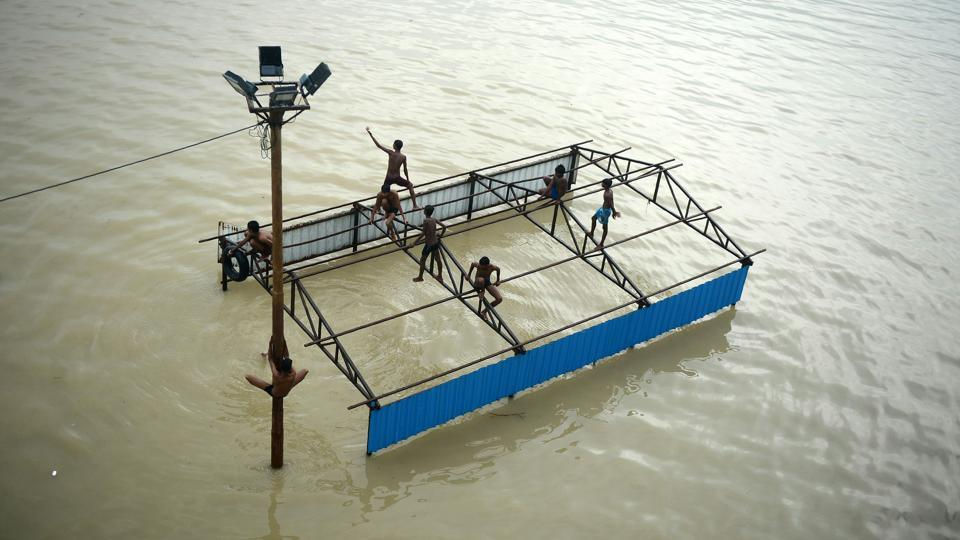Children play atop submerged restroom at Daraganj Ghat as they bathe on the flooded banks of the Ganga river in Allahabad, Uttar Pradesh on September 11, 2018. (Sanjay Kanojia / AFP)