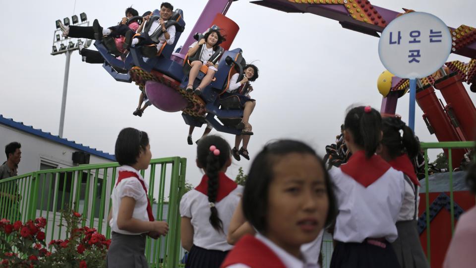 People enjoy a ride at an amusement park in Pyongyang, North Korea. (Dita Alangkara / AP)